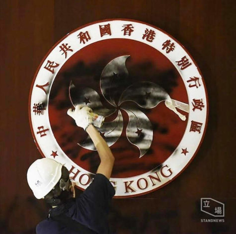 A pro-democrocy protester sprays black spray-paint on the emblem of the Hong Kong Special Administrative Region inside the Legislative Council Chamber on July 1, 2019. Photo Credit: The Stand News.